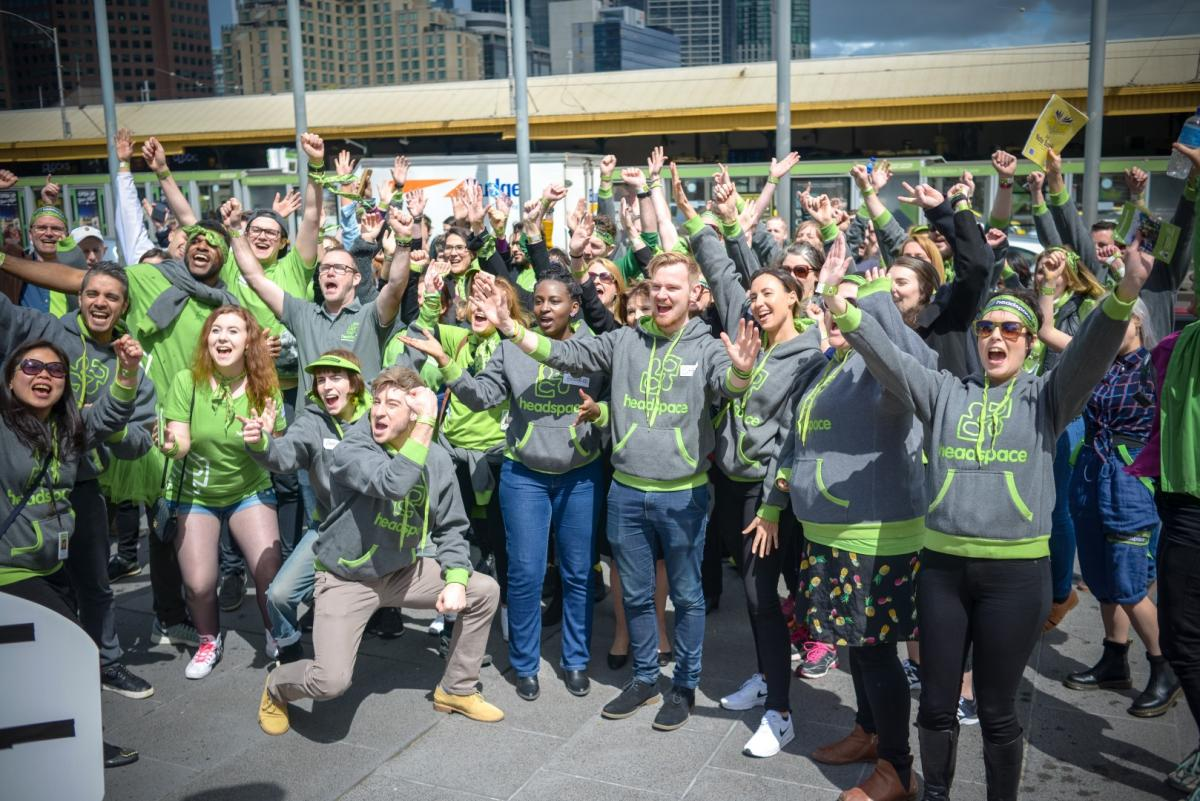 Large group of people in headspace branded clothing waving their arms up outside on headspace day